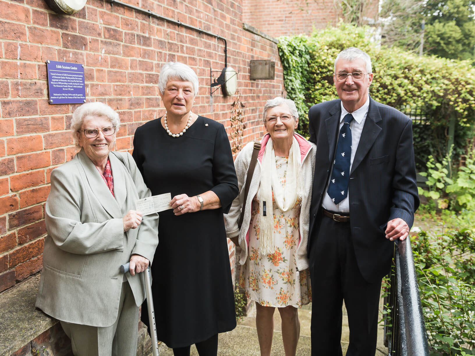 Jacqui Green (left), leader of the Park Street Mission from 1969 - 2018, hands a cheque from the sale of their Park Street building to Dame Janet Trotter, Chair of Trustees at The Nelson Trust, with Park Street Mission Trustees Pat and Andrew Turrall (right).